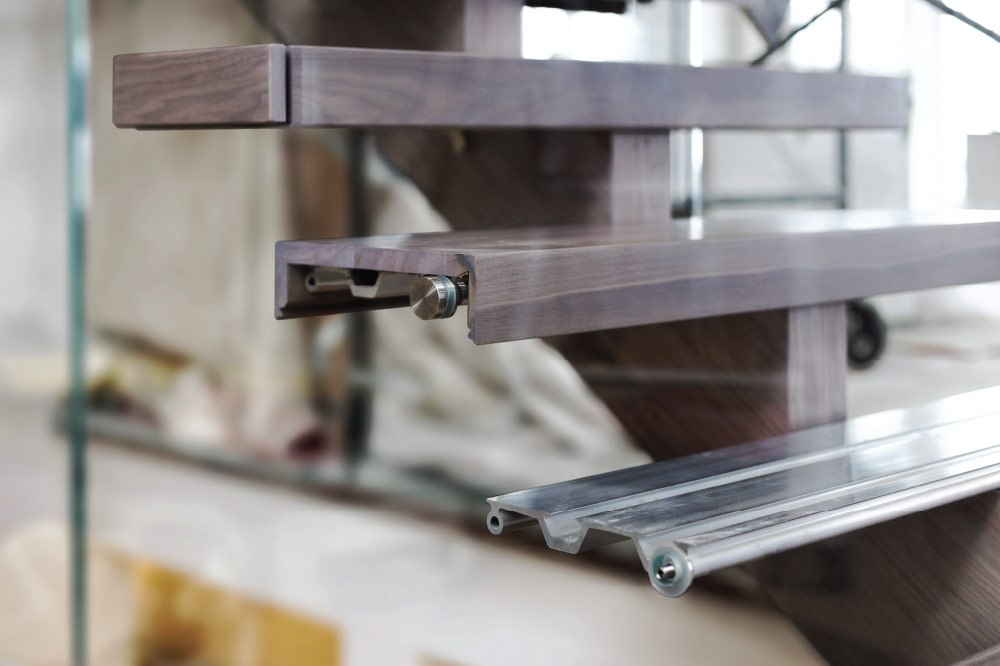 mono-stringer stair installation / metal step support / glass standoffs attached to metal step support / wood step liner
